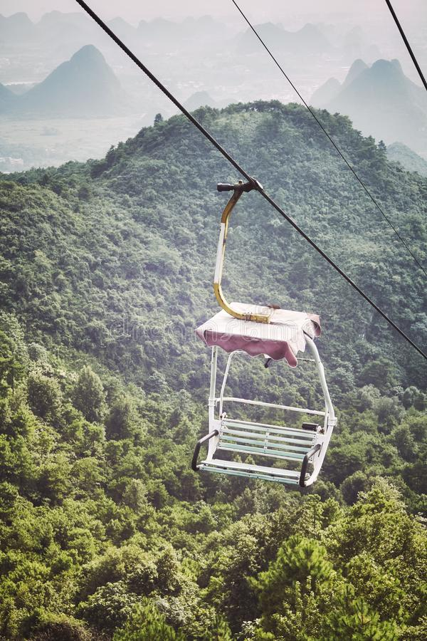 Retro toned picture of an old chairlift in Karst Mountains, China. Retro toned picture of an old chairlift in Karst Mountains, Guilin, China stock images