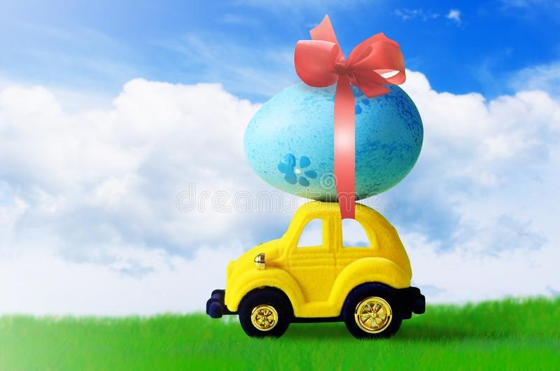 Retro toy car with Easter egg on the roof on spring background. Easter concept. Retro toy car with Easter egg on the roof. on spring background Easter concept royalty free stock photography