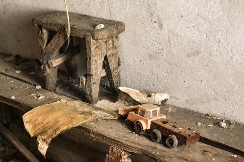 Retro toy car, wooden stool and piece of dirty paper, part abandoned house interior. Forgotten place. royalty free stock photo