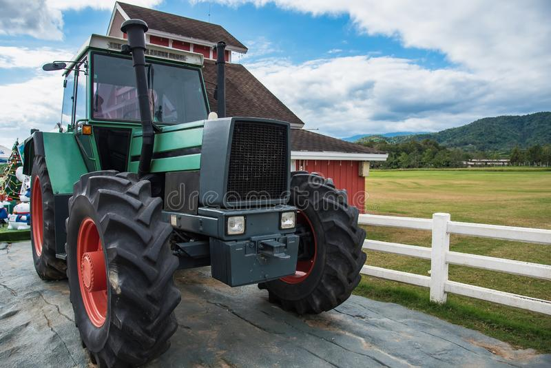 A retro tractor parked next to a barn in a farm.Thailand. Green vintage summer sky vehicle transportation engine harvest agricultural agriculture antique cloud royalty free stock photo