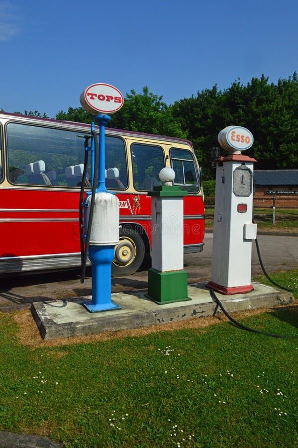 Retro trasporto di bus rosso e pompe di benzina antiquate fotografie stock libere da diritti