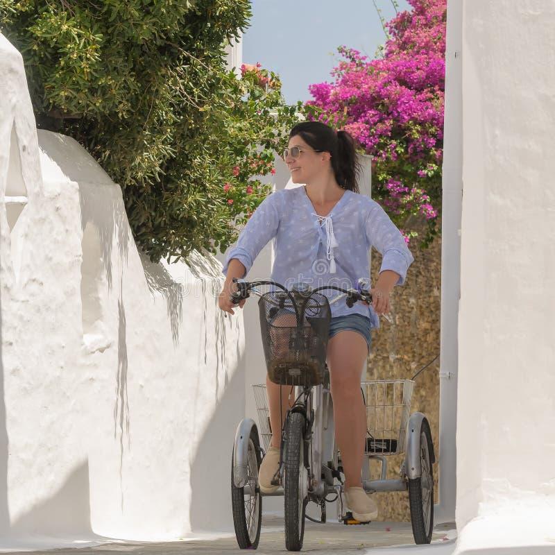Retro trehjuling i en grafisk gränd på den Andros ön i Grekland med en kvinnamodell överst fotografering för bildbyråer