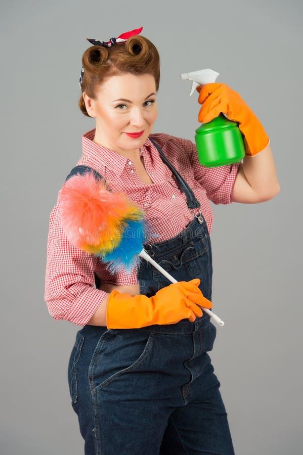 Retro trucco femminile con spruzzo a disposizione Pulizia della ragazza del denim con lo spruzzo e lo spolveratore in studio su f fotografie stock libere da diritti