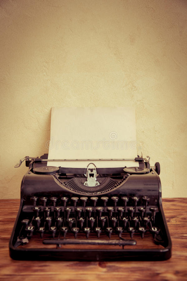 Retro typewriter. With paper blank on wood table. Top view royalty free stock photo