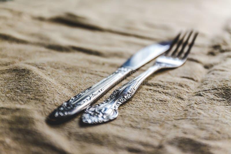 retro uitstekende bestekmes en vork op antiek tafelkleed stock fotografie