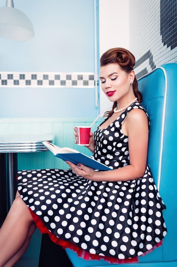 Retro uitstekende portret van verleidelijke jonge meisjeszitting in koffie en de lezing boeken Speld op stijlportret van jong mei stock foto's