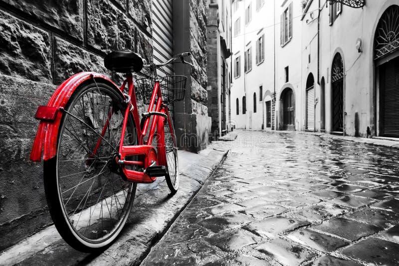 Retro uitstekende rode fiets op keistraat in de oude stad Kleur in zwart-wit stock foto