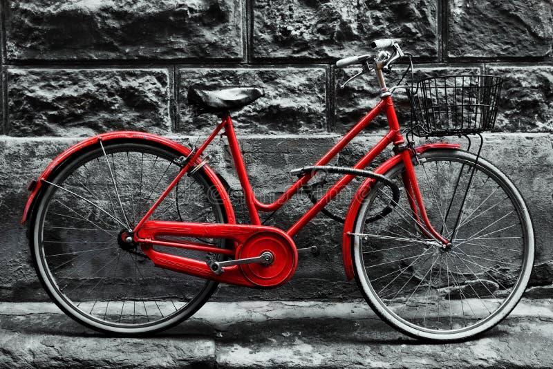 Retro uitstekende rode fiets op zwart-witte muur stock fotografie