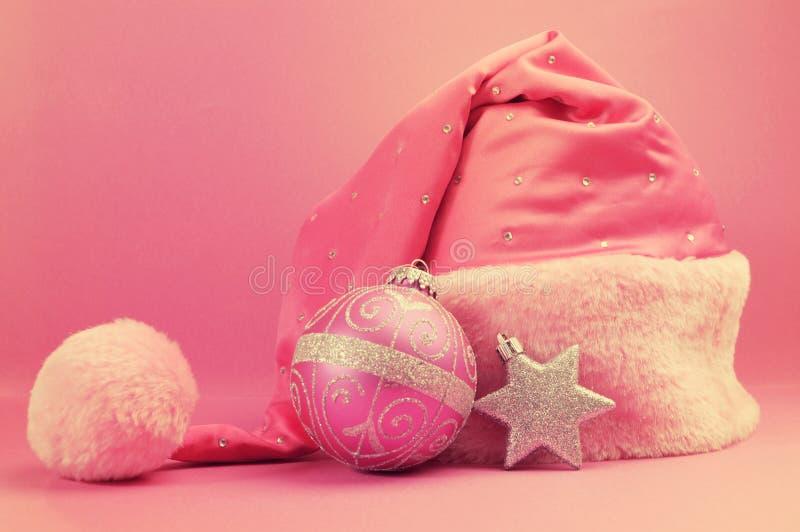Retro uitstekende roze santahoed met feestelijk Kerstmisornament stock afbeelding