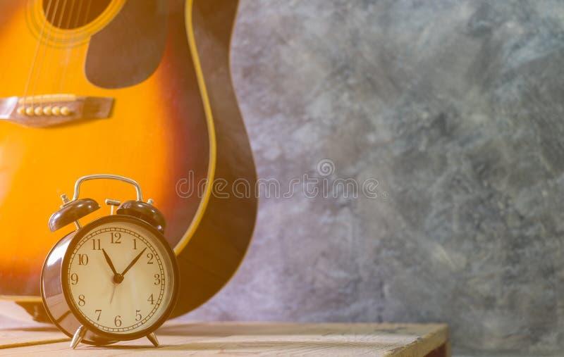 Retro uitstekende stijl van de alarm zwarte klok en Akoestische gitaar die tegen op houten lijst een lege achtergrond van de ceme royalty-vrije stock foto's