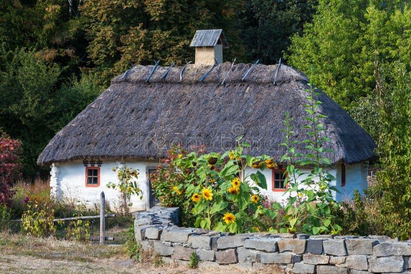 Retro ukrainian cottage with thatched roof. In Pirogovo village, Kiev region, Ukraine royalty free stock image