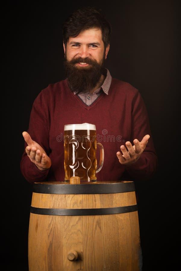 Retro uomo con una birra Fabbricante di birra felice sul barilotto di birra con i vetri di birra Birra fotografia stock libera da diritti