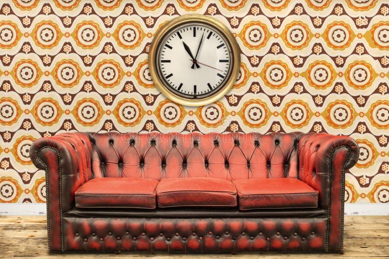 Retro utformad bild av en gammal soffa och klocka mot en tappningwa arkivfoton