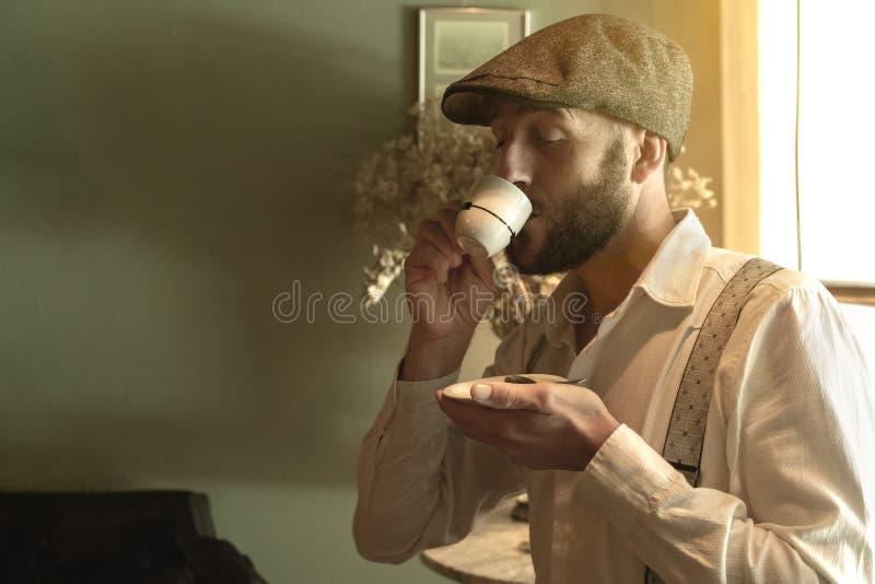 Retro utformad man som smakar ett kaffe i en tappningmilj? royaltyfri fotografi