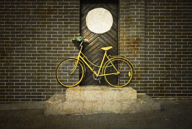 Retro vecchia bici gialla d'annata sulla via fotografia stock
