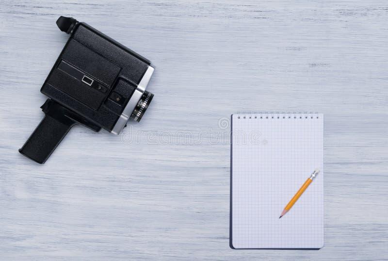 Retro videocamera op een lichtgrijs bureau, met een blad van geruit document en een eenvoudig potlood, met ruimte voor opname royalty-vrije stock fotografie