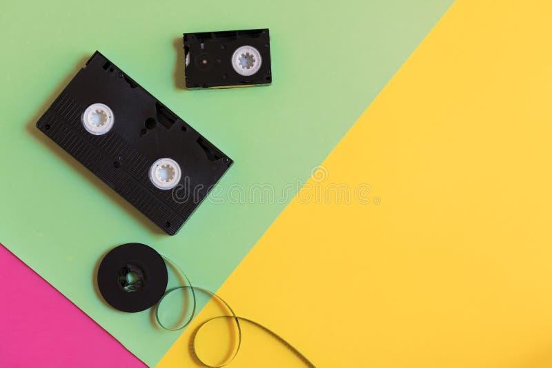 Retro- Videokassette und Film auf einem DreiFARBpastellpapierhintergrund Flache Lage, minimales Konzept lizenzfreie stockfotografie