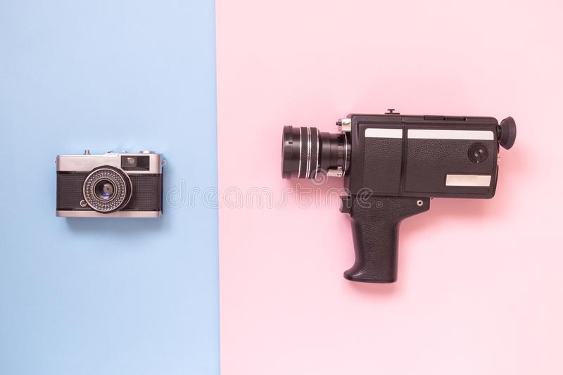 Flat lay of old fashioned camcorder and camera against pastel background minimalistic concept. royalty free stock photography