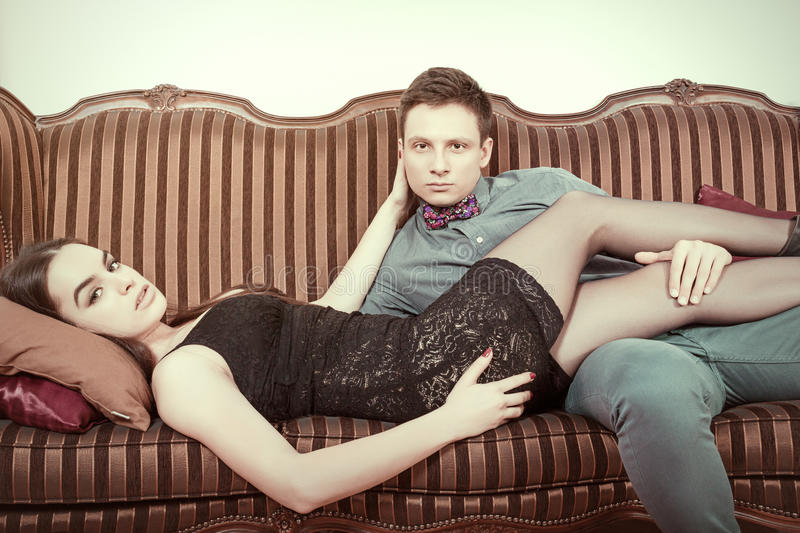 Retro vintage couple lying on the retro furniture. Young men and women In edition looking seductively at camera or at you. Vintage male and female model on stock photo