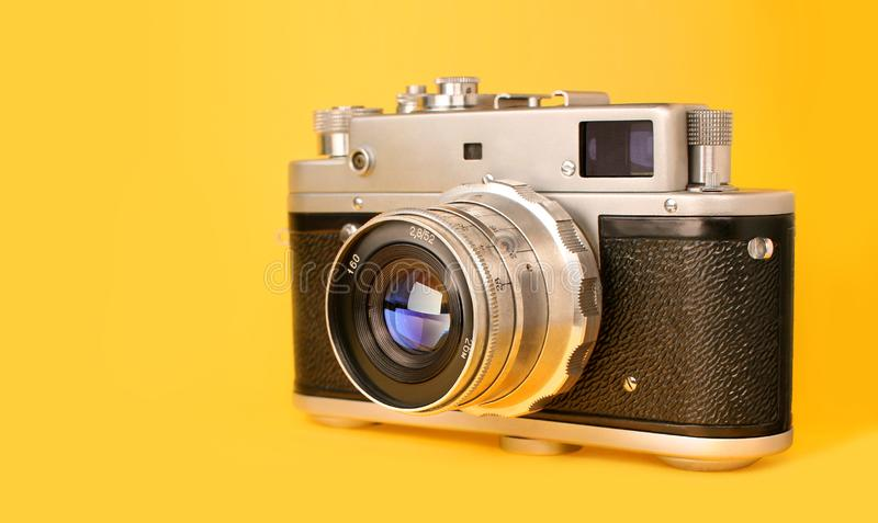 Retro, vintage film photo camera isolated on yellow colourful trendy modern fashion background. Camera lens with stock images