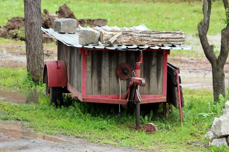 Retro vintage homemade tractor trailer with metal and wooden boards frame left in muddy backyard covered with sheet metal. Held in place with wooden log and stock photo