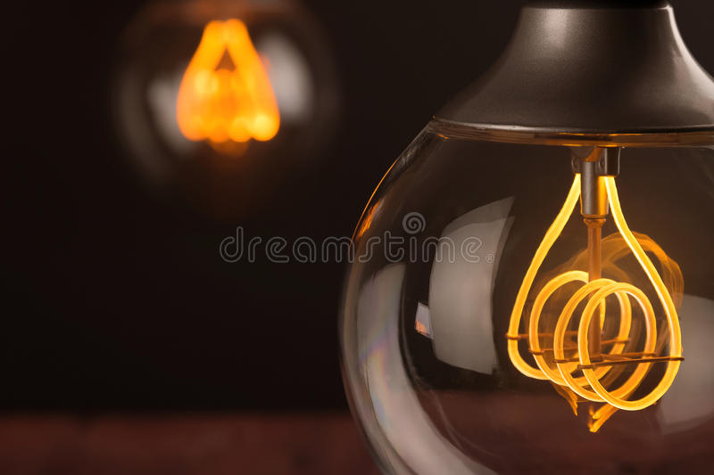 Retro vintage light bulb with led technology bult-in on warm light yellow tint and black background, energy saving with old style. Atmosphere concept stock images