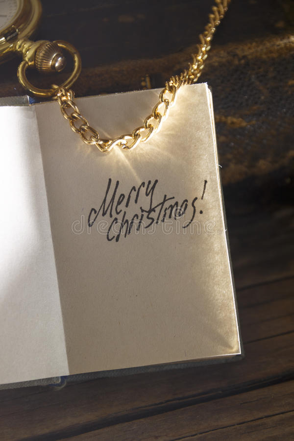 Retro Vintage Merry Christmas Greeting Card. Merry Christmas - inscription, gold pocket watch and old vintage book royalty free stock image