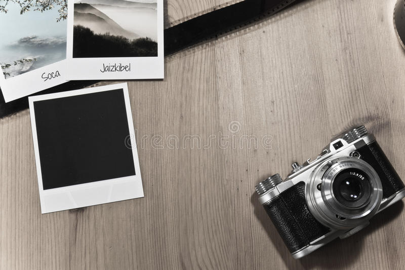 Retro vintage photography concept of three instant photo frames cards on wooden background with old camera and film strip. Retro vintage photography concept of stock photography