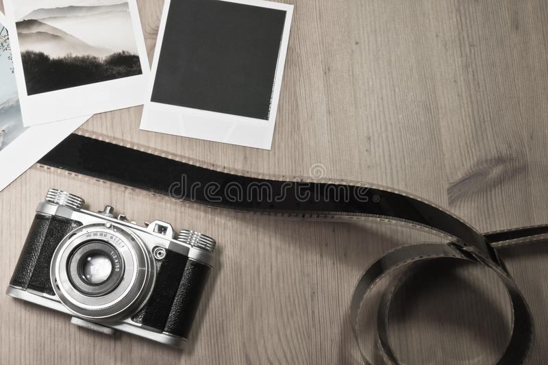 Retro vintage photography concept of three instant photo frames cards on wooden background with old camera and film strip. Retro vintage photography concept of stock images