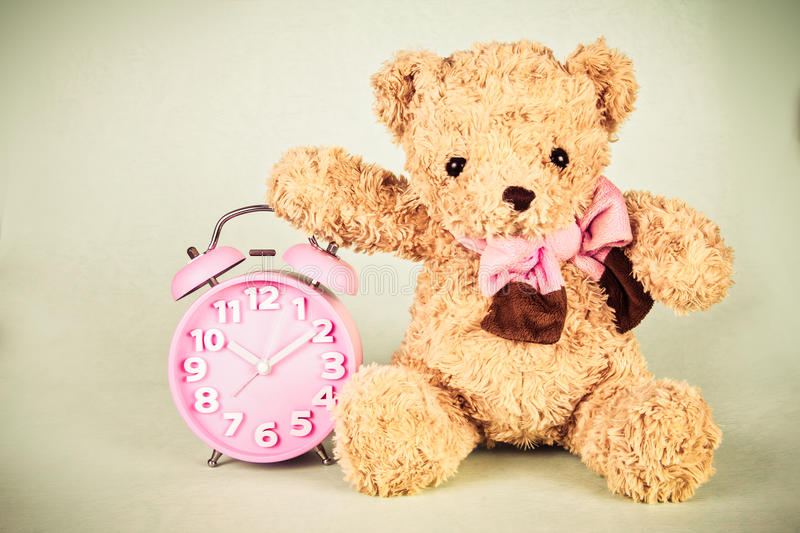Retro and vintage style of Old fashioned alarm clock and cute br. Retro and vintage style of the Old fashioned alarm clock and cute brown bear doll royalty free stock images