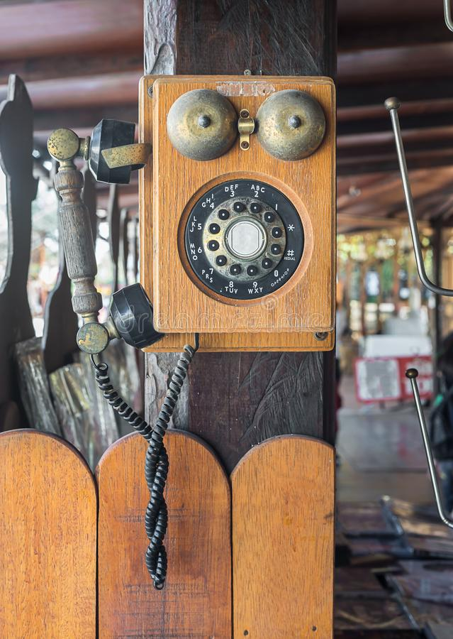 Vintage telephone hang on wooden pole royalty free stock image