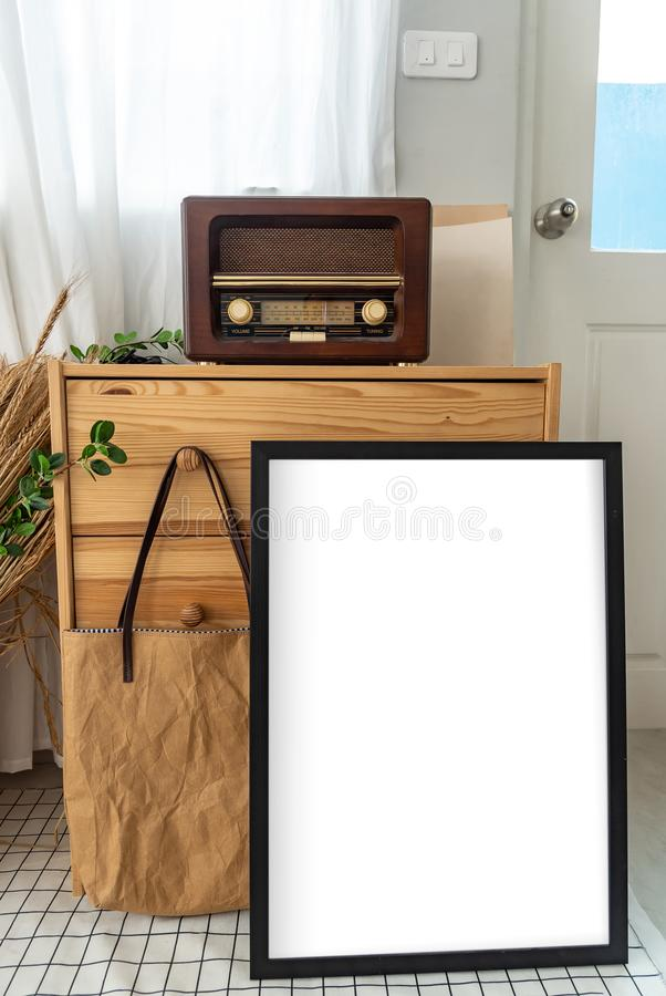 Retro vintage transistor radio is on a wooden locker which there is a blank white frame for text  advertisement .Interior vintage royalty free stock images