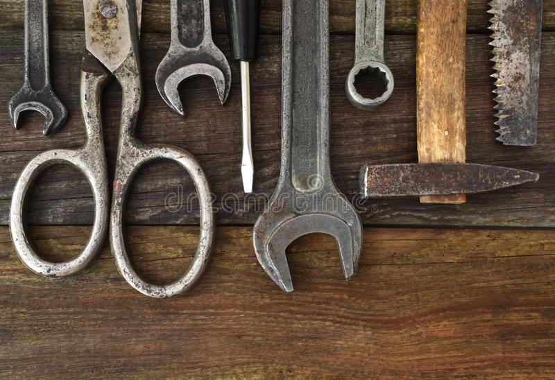 Retro vintage woodwork equipment set. Hammer scissors screwdriver on brown texture wooden planks background. Old stock photography