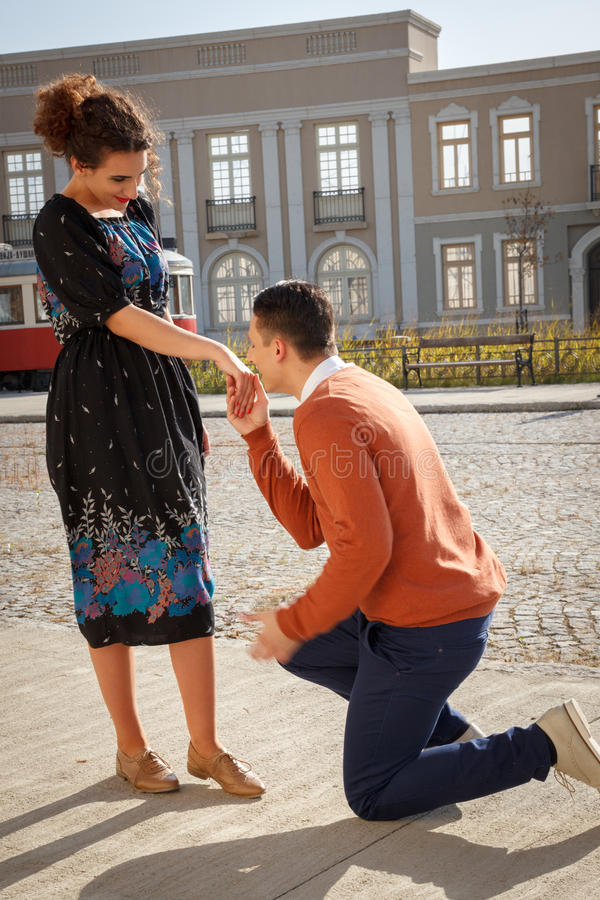 Retro vintage young man kneeling and asking a girl to marry him stock photo