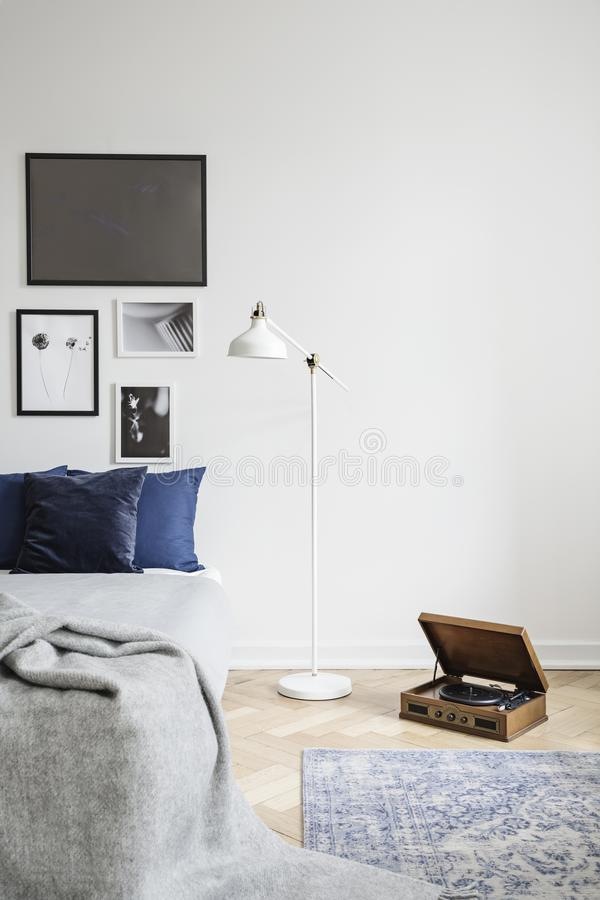 Retro vinyl record player and an industrial style floor lamp in a hipster bedroom with framed picture stock photo