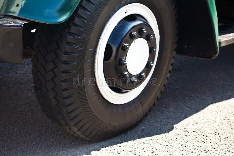 Retro vrachtwagenwiel, asfaltachtergrond Rijpe zaden van granaatappel Zachte nadruk Het oude deel van de stijlauto royalty-vrije stock afbeeldingen