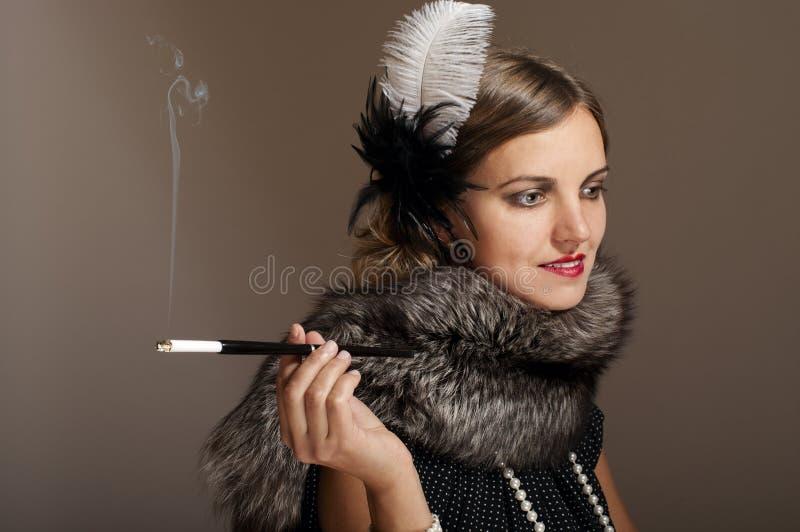 Retro vrouw in bont met sigaret stock afbeelding