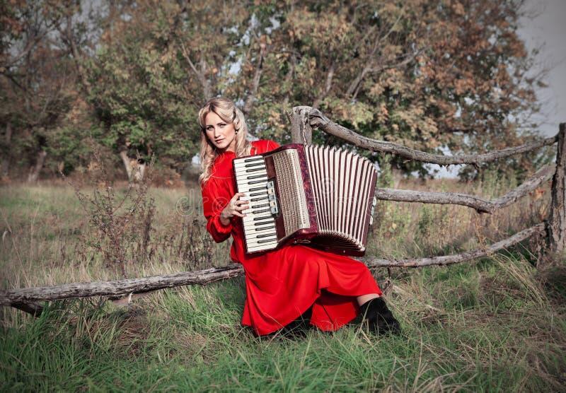 Retro vrouw in traditioneel kostuum met een harmonika royalty-vrije stock afbeeldingen