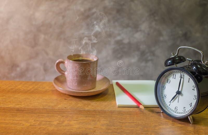 Retro- Warnungsschwarzuhr-Weinleseart mit dem leeren offenen Buch, rotem Bleistift und dem Schalenkaffeepastellrosa alt auf Holzt lizenzfreie stockfotos