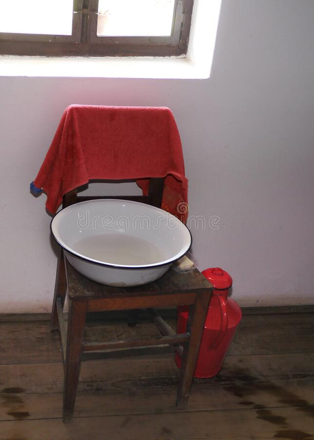 Retro washing basin on a chair with red towel royalty free stock photography