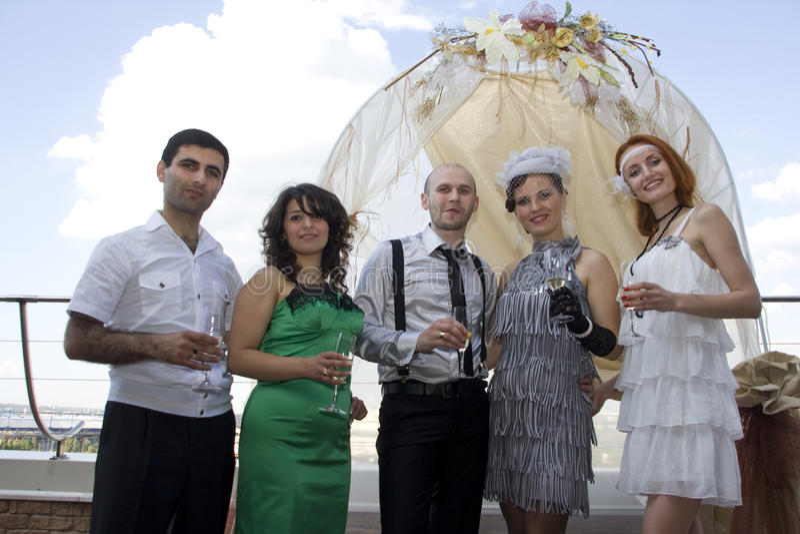 Retro wedding. Bride, groom and guests royalty free stock image