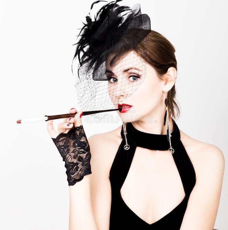 Retro- weibliches Modell der Schönheit mit Berufsmake-up und Mundstück in der Hand stockbilder