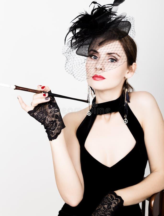 Retro- weibliches Modell der Schönheit mit Berufsmake-up und Mundstück in der Hand stockfotografie