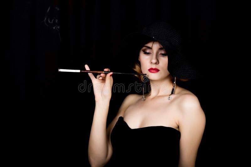Retro- weibliches Modell der Schönheit mit Berufsmake-up und Mundstück in der Hand Modeweinlesefrau auf einem dunklen Hintergrund stockbild