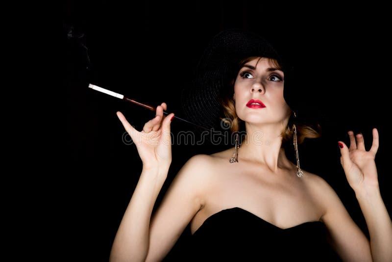 Retro- weibliches Modell der Schönheit mit Berufsmake-up und Mundstück in der Hand Modeweinlesefrau auf einem dunklen Hintergrund lizenzfreies stockbild