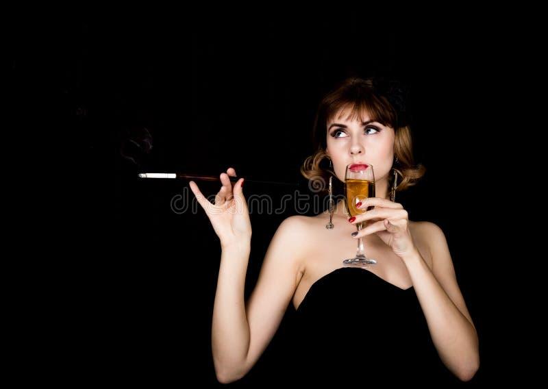 Retro- weibliches Modell der Schönheit mit dem Berufsmake-up, das Mundstück und Glas Champagner hält Modeweinlesefrau auf a lizenzfreie stockfotos