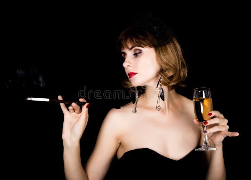 Retro- weibliches Modell der Schönheit mit dem Berufsmake-up, das Mundstück und Glas Champagner hält Modeweinlesefrau auf a lizenzfreie stockfotografie