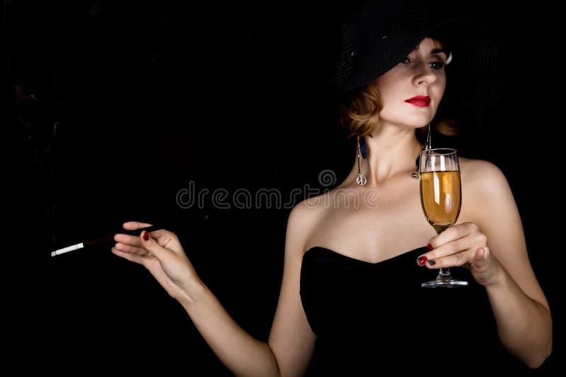 Retro- weibliches Modell der Schönheit mit dem Berufsmake-up, das Mundstück und Glas Champagner hält Modeweinlesefrau auf a stockfotos