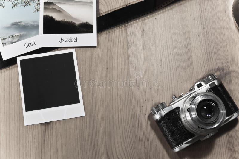 Retro- Weinlesephotographiekonzept von drei sofortigen Fotorahmenkarten auf hölzernem Hintergrund mit altem Kamera- und Filmstrei stockfotografie
