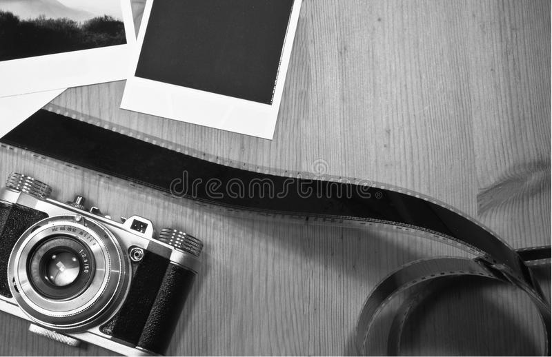 Retro- Weinlesephotographiekonzept von zwei sofortigen Fotorahmenkarten auf hölzernem Hintergrund mit altem Kamera- und Filmstrei stockfoto